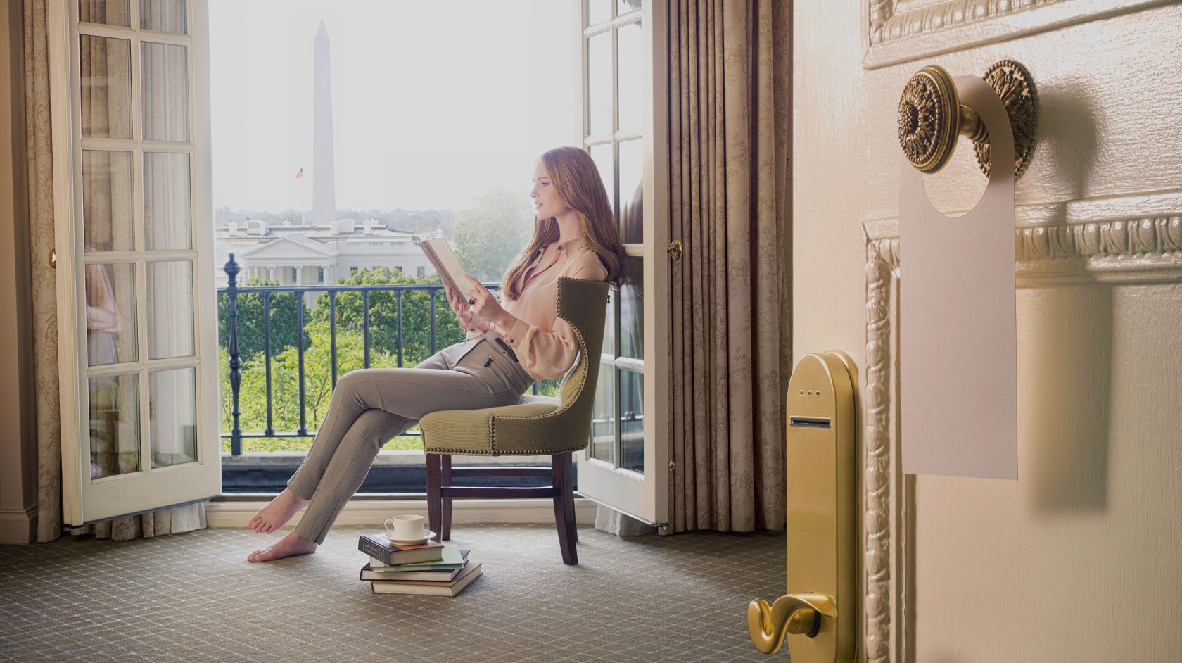 Woman at Hay Adams reading a book overlooking the Washington Monument