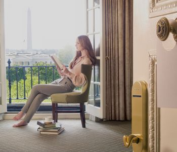 Woman at Hay Adams reading a book overlooking the Washington Monument in Washington D.C.