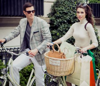 Glamorous couple riding bikes in from of The Hay-Adams