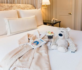 Stuffed Bear, Robe & Toys Spread on Bed at Hay Adams