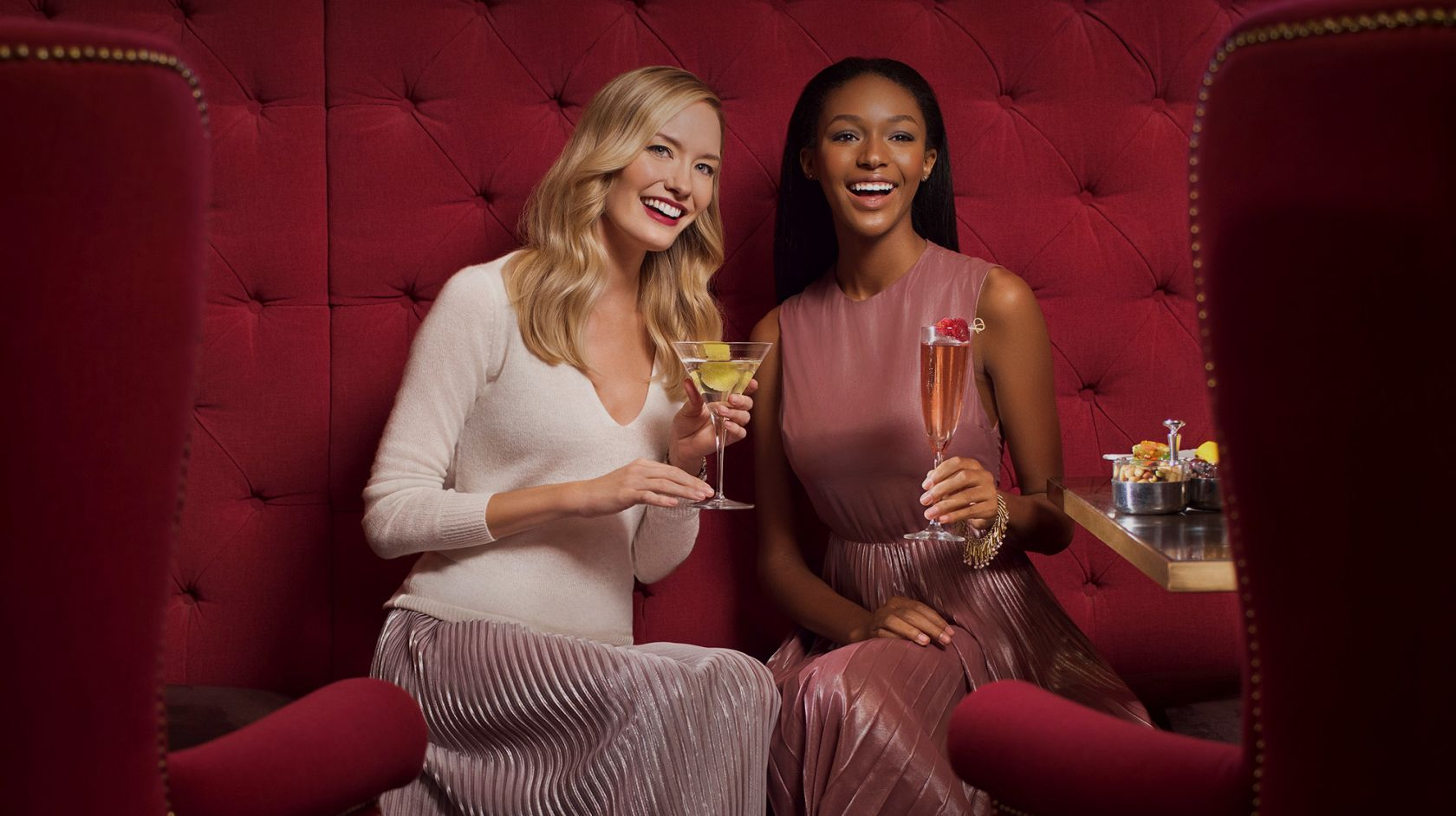 Two women sitting in a booth and smiling and holding cocktails at Off the Record