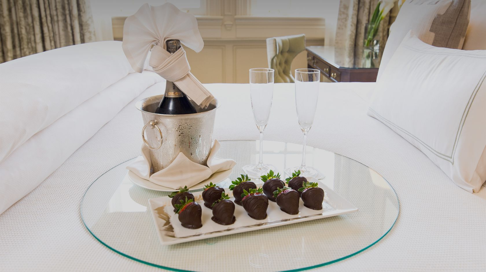 a tray of chocolate covered strawberries and champagne with two flutes sitting on a bed